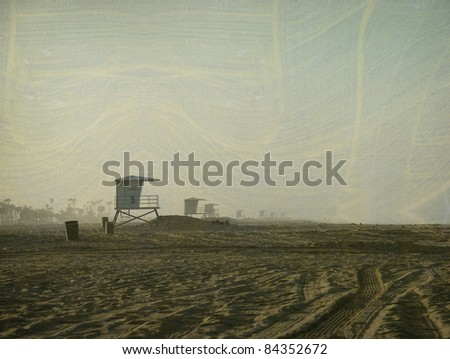 aged and worn vintage photo of early morning beach landscape with lifeguard tower - stock photo