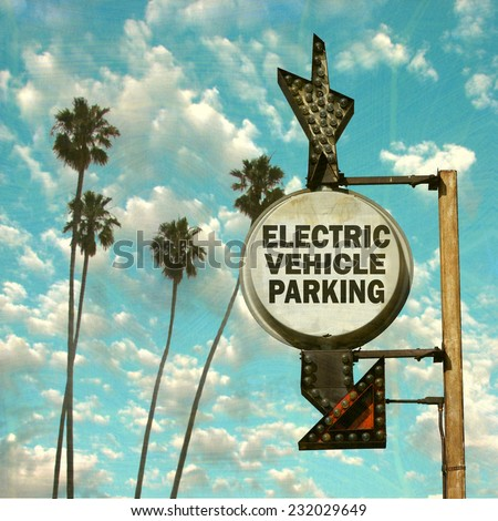 aged and worn vintage photo of electric vehicle parking sign                             - stock photo