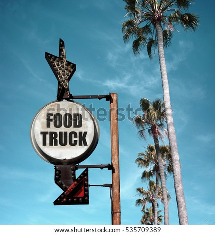 aged and worn vintage photo of food truck sign and palm trees