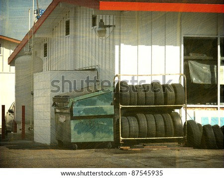 aged and worn vintage photo of gas station with old tires - stock photo