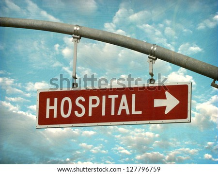 aged and worn vintage photo of  hospital street sign - stock photo