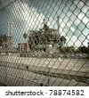 aged and worn vintage photo  of industrial factory behind fence - stock photo