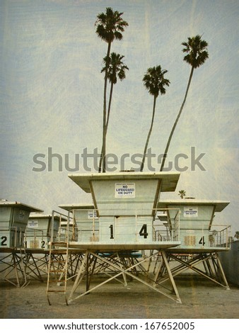 aged and worn vintage photo of lifeguard tower and palm trees                               - stock photo
