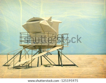 aged and worn vintage photo of lifeguard tower on beach sand - stock photo