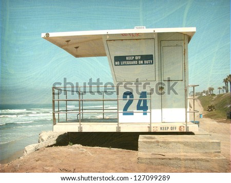 aged and worn vintage photo of  lifeguard tower overlooking beach - stock photo
