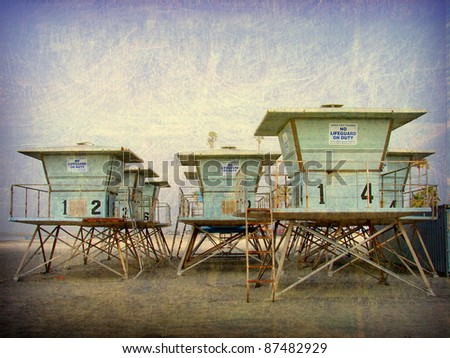 aged and worn vintage photo of  lifeguard towers on beach - stock photo