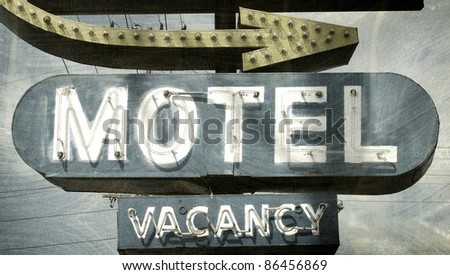 aged and worn vintage photo of motel sign with arrow - stock photo
