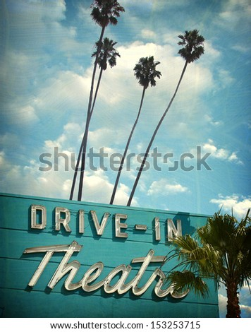 aged and worn vintage photo of neon drive in sign                              - stock photo