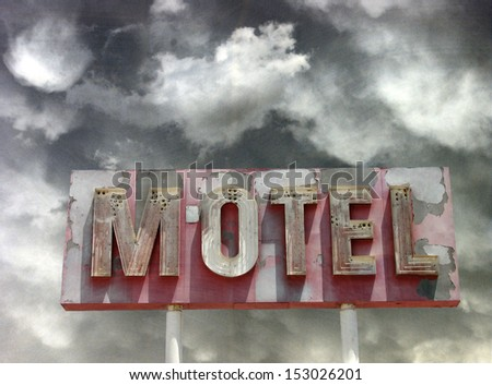 aged and worn vintage photo of neon motel sign and dramatic sky                               - stock photo