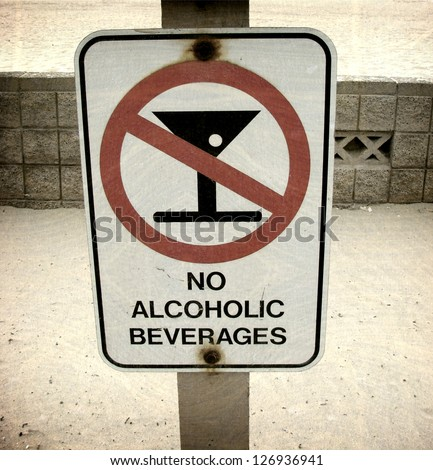 aged and worn vintage photo of  no alcoholic beverages sign on beach - stock photo