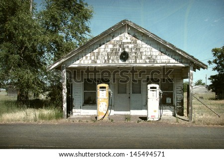 aged and worn vintage photo of old gas station and pumps                              - stock photo