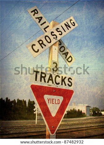 aged and worn vintage photo of  railroad crossing warning sign - stock photo