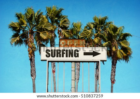 aged and worn vintage photo of surfing sign with palm trees