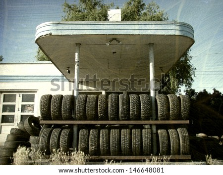 aged and worn vintage photo of tires at old service station                               - stock photo