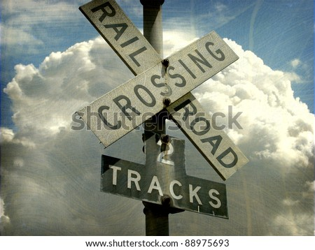 aged and worn vintage photo of  2 tracks railroad crossing sign - stock photo