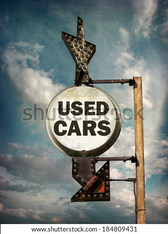 aged and worn vintage photo of used cars sign with arrow                               - stock photo
