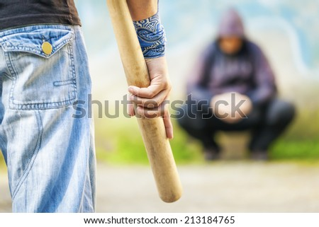 Aggressive man with a baseball bat against other man