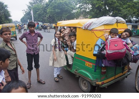 AHMEDABAD, INDIA - SEPTEMBER 7: Unidentified children travel from a school by a rickshaw at September 7, 2011 in Ahmedabad, India. Education is free for children for 6 to 14 years of age in India. - stock photo