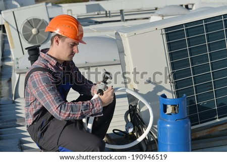 Air Conditioning Repair, young repairman on the roof fixing air conditioning system. Model is actual repairman / electrician.