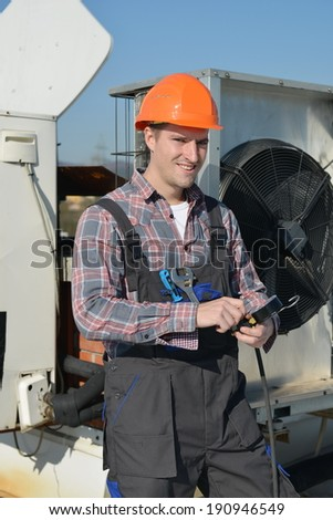 Air Conditioning Repair, young repairman on the roof fixing air conditioning system. Model is actual repairman / electrician.  - stock photo