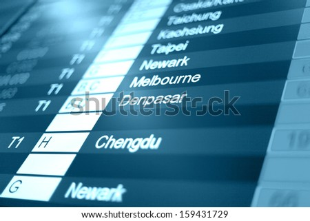 Airport arrival board in airport terminal. Travel concept. Denpasar in focus. - stock photo