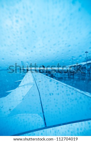 airport in the rain,view from airliner window - stock photo