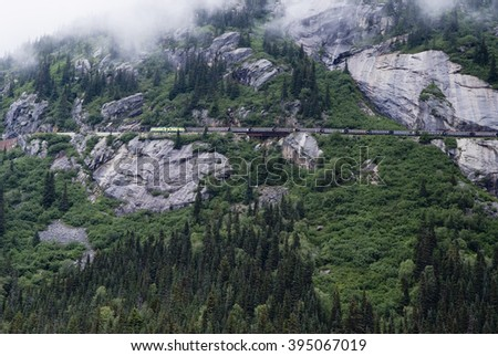 Alaska White Pass And Yukon Route Railroad Train Travelling Along Mountain Route - stock photo