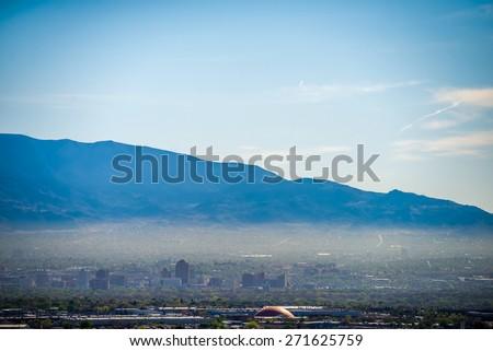 Albuquerque new mexico skyline in smog  with mountains - stock photo