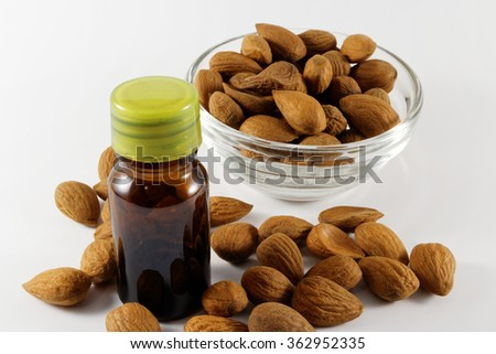 Almond in glass dish and almond oil in small brown bottle on white background  - stock photo