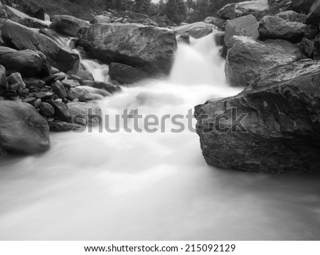 Alpine brook in steep stony stream bed. Noisy waves of stream running over boulders and stones,  high water level after heavy rains. - stock photo