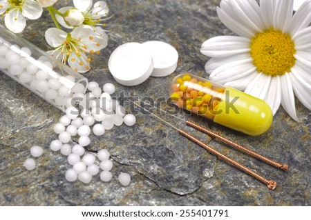 alternative medicine with herbal pills and acupuncture - stock photo
