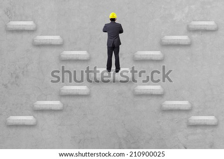 alternative staircase go to rear view businessman standing cross one's arm and yellow helmet for workers security conceptual step by step of business to creativity for success  - stock photo