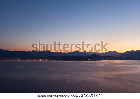 05 AM, coast of Corsica, France. Calm sea with first rays of sun - stock photo