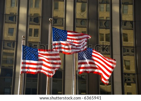 3 american flags against building