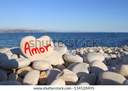 �¢??Amor�¢?� written on heart shaped stone on the beach - stock photo