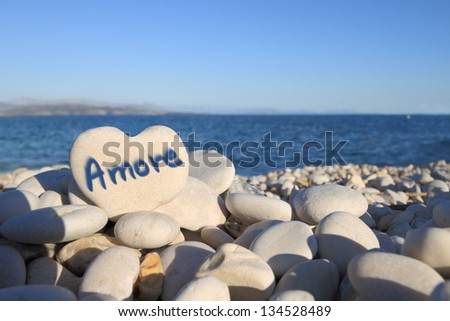 """""""Amore�¢?� written on heart shaped stone on the beach - stock photo"""
