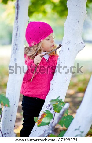 amusing little girl drawing on a tree - stock photo