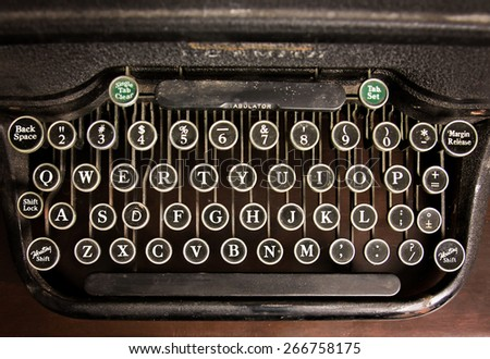 an antique typewriter on a wooden table  - stock photo