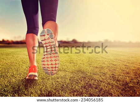 an athletic pair of legs on grass during sunrise or sunset - healthy lifestyle concept  - stock photo