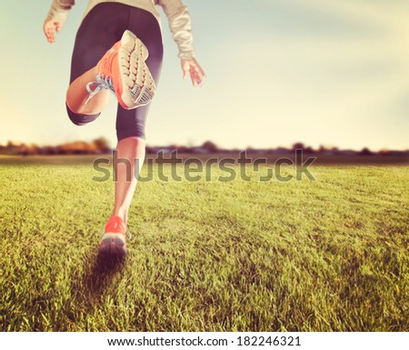 an athletic pair of legs on grass during sunrise or sunset - healthy lifestyle concept done with a soft instagram like filter - stock photo