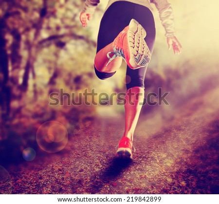 an athletic pair of legs running on a path during sunrise or sunset - healthy lifestyle concept done with a retro vintage instagram filter  - stock photo