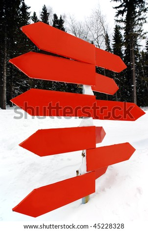 An isolated signpost, in snowy mountains, space for text on the sign - stock photo