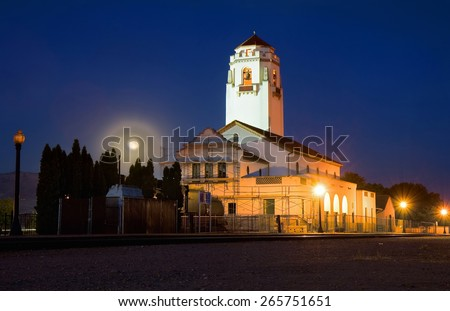 an old train depot with empty tracks at night with the moon rising behind  - stock photo