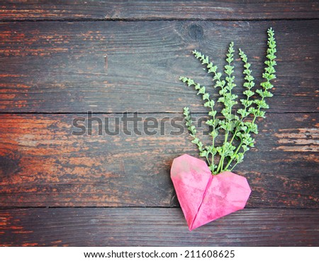 an origami heart on old fence boards - good for valentine's day or background design - stock photo