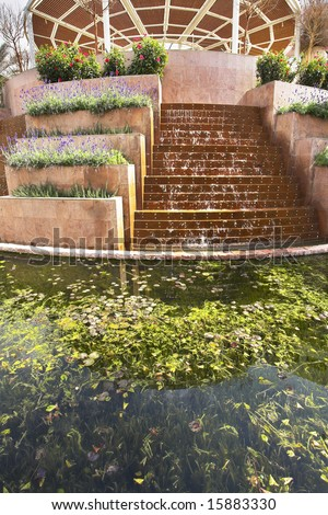 An original fountain and flower beds in a court yard of fine hotel on Red sea - stock photo