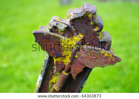 Ancient cross with butterfly in an old cemetery - stock photo