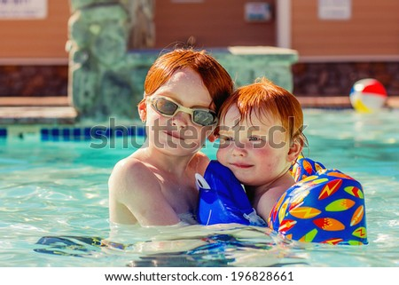 6 and 2 year old brothers swimming in a pool with a flotation device--image taken outdoors using natural light (Reno, Nevada, USA) - stock photo