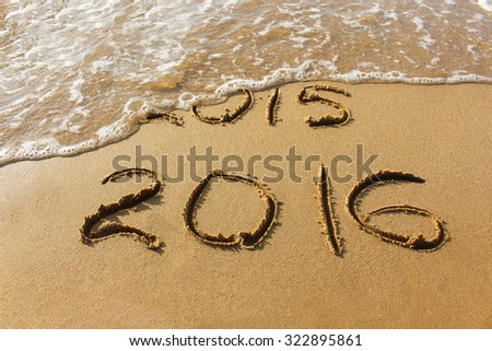 2015 and 2016 year written on sandy beach sea.  Wave washes away 2015. The concept of 2015 is gone, come the new year 2016. - stock photo