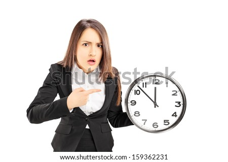 Angry young businesswoman pointing on a wall clock, isolated on white background - stock photo