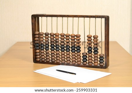 Antique wooden abacus for accountants on the table, sheets of paper and a pen in still life - stock photo